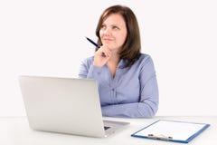 La empresaria se está sentando delante de un ordenador portátil Fotos de archivo libres de regalías