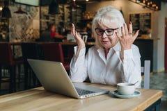 La empresaria se está sentando en una tabla delante de un ordenador portátil, está llevando a cabo sus manos ascendentes y está m Imágenes de archivo libres de regalías