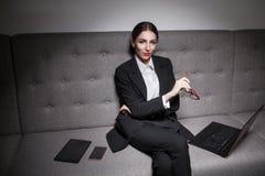 La empresaria se vistió en traje y con el ordenador portátil, el teléfono y la tableta; Fotos de archivo libres de regalías