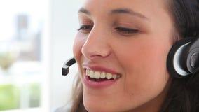 La empresaria sonríe mientras que ella habla en auriculares Imagenes de archivo