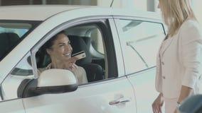 La empresaria sonriente da una tarjeta de crédito al encargado en salón auto almacen de metraje de vídeo