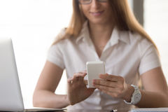 La empresaria sonriente que sostiene el smartphone blanco, hembra da ingenio Imagen de archivo