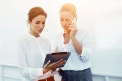 La empresaria transmite la información sobre el teléfono móvil mientras que el socio que sostiene la almohadilla táctil delante d Imagen de archivo libre de regalías