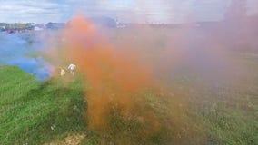 La encuesta aérea de pares camina en el campo con humo coloreado en manos El volar sobre hombre y la mujer corren a través del ca Fotos de archivo