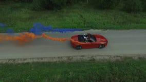 La encuesta aérea del rojo cabrioled va en el camino y los pares usando humo coloreado El volar sobre el coche convertible rojo c almacen de metraje de vídeo
