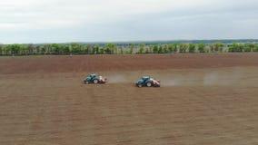 La encuesta a?rea, primavera, all? es dos tractores en el campo con los plantadores especiales de la precisi?n, se planta el ma?z almacen de metraje de vídeo
