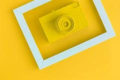 La endecha plana de la cámara amarilla del vintage y la foto enmarcan el fondo Imagen de archivo libre de regalías
