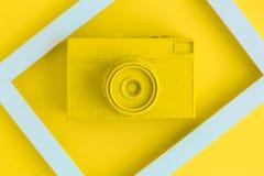 La endecha plana de la cámara amarilla del vintage y la foto enmarcan el fondo Fotografía de archivo libre de regalías