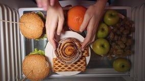 La endecha plana de la mano toma la comida en la noche con en los estantes del refrigerador metrajes