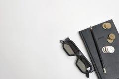 La endecha plana del cuaderno, de la pluma, de vidrios y de la rublo negros acuña en superficie de madera con el espacio de la co Fotografía de archivo