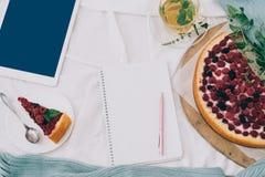 La endecha plana entonó el desayuno en cama con el pastel de queso de la frambuesa, el té y el cuaderno abierto, tableta de la me Fotografía de archivo libre de regalías