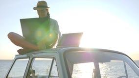 La energía solar, la sentada femenina en el coche del vintage con el cuaderno y la batería en el cielo en luz del sol, muchacha d