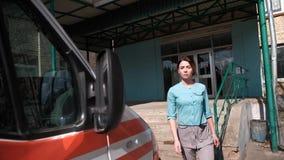 La enfermera acomete a la ambulancia en el campo almacen de video