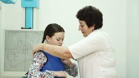 La enfermera ayuda a poner el chaleco protector en gabinete de la radiografía en hospital almacen de video