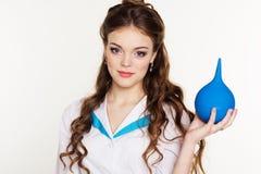 La enfermera bonita joven de la muchacha con el azul arroja a chorros en manos Imágenes de archivo libres de regalías