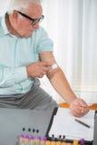 La enfermera con la jeringuilla está tomando la sangre para la prueba en la oficina del doctor Fotografía de archivo libre de regalías