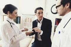 La enfermera da píldoras y el vidrio de agua al paciente que mira al doctor Tomar píldoras fotos de archivo libres de regalías