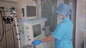 La enfermera de la mujer prepara el aparato innovador electrónico para la operación quirúrgica 4K metrajes