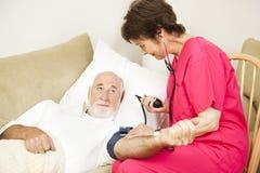 La enfermera de salud casera toma la presión arterial Imagen de archivo libre de regalías