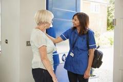 La enfermera en la visita casera saluda a la mujer mayor en su puerta principal imágenes de archivo libres de regalías