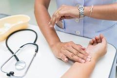La enfermera es pulso radial de la medida en la muñeca del paciente foto de archivo libre de regalías