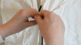 La enfermera está ayudando al doctor a prepararse a la cirugía en el hospital vistiéndolo en frente almacen de video