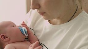 La enfermera está oscilando al bebé recién nacido en las manos almacen de video