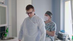 La enfermera está preparando a un paciente con estéril viste antes de cirugía ortodóntica almacen de metraje de vídeo