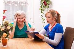 La enfermera hace a casa datos de la visita y del expediente Foto de archivo libre de regalías