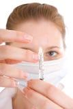 La enfermera joven con una jeringuilla aislada Imagen de archivo libre de regalías