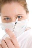 La enfermera joven con una jeringuilla aislada Imágenes de archivo libres de regalías