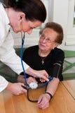 La enfermera mira a la mujer mayor en una clínica de reposo Foto de archivo libre de regalías