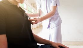 La enfermera que escucha el patient& masculino x27; pecho de s foto de archivo