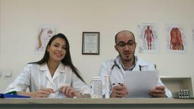 La enfermera y el varón sonrientes cuidan hablar con la cámara almacen de metraje de vídeo