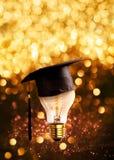 la enhorabuena gradúa el casquillo en un bulbo de lámpara con las luces del brillo foto de archivo libre de regalías