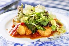 La ensalada con el prendedero de pescados frito, la pimienta roja y la ensalada se mezclan Foto de archivo libre de regalías