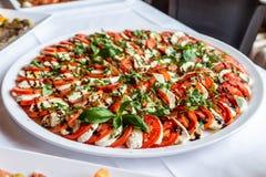 La ensalada de Caprese con el tomate de la mozzarella, la albahaca y el vinagre balsámico arregló en la placa blanca imagen de archivo