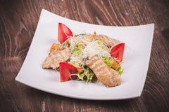 La ensalada de Cesar con chiken, tomate, los cuscurrones y queso Imagen de archivo libre de regalías