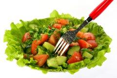La ensalada de tomates, de pepinos y del eneldo en lechuga se va con una bifurcación Fotografía de archivo