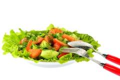La ensalada de tomates, de pepinos y del eneldo en lechuga se va con una bifurcación de la cuchara Imagenes de archivo