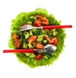 La ensalada de tomates, de pepinos y del eneldo en lechuga se va con una cuchara y una bifurcación Fotografía de archivo