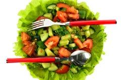 La ensalada de tomates, de pepinos y del eneldo en lechuga se va con una cuchara y una bifurcación Foto de archivo libre de regalías