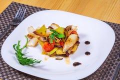 La ensalada de verduras asadas a la parrilla en una placa blanca adornó las hierbas Fotografía de archivo