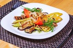 La ensalada de verduras asadas a la parrilla en una placa blanca adornó las hierbas Imagen de archivo libre de regalías
