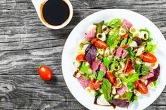 La ensalada deliciosa con las hojas mezcladas de la lechuga, salami de las pastas de Shell en el plato blanco con las semillas de Imagenes de archivo