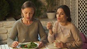 La ensalada femenina del vegano de la consumición, su amigo prefiere el postre cremoso, eligiendo la nutrición metrajes