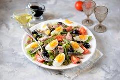 La ensalada francesa Nicoise con el atún, patatas hervidas, huevo, habas verdes, tomates, secó aceitunas, lechuga y las anchoas Fotos de archivo libres de regalías