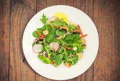La ensalada fresca de la primavera con el rábano, Mizuno, setas asó a la parrilla, queso del Adygei, espinaca, paprika, limón, ma Foto de archivo
