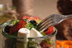 La ensalada griega sirvió en el tarro de cristal con los ingredientes Imagen de archivo