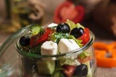 La ensalada griega sirvió en el tarro de cristal con los ingredientes Imagen de archivo libre de regalías